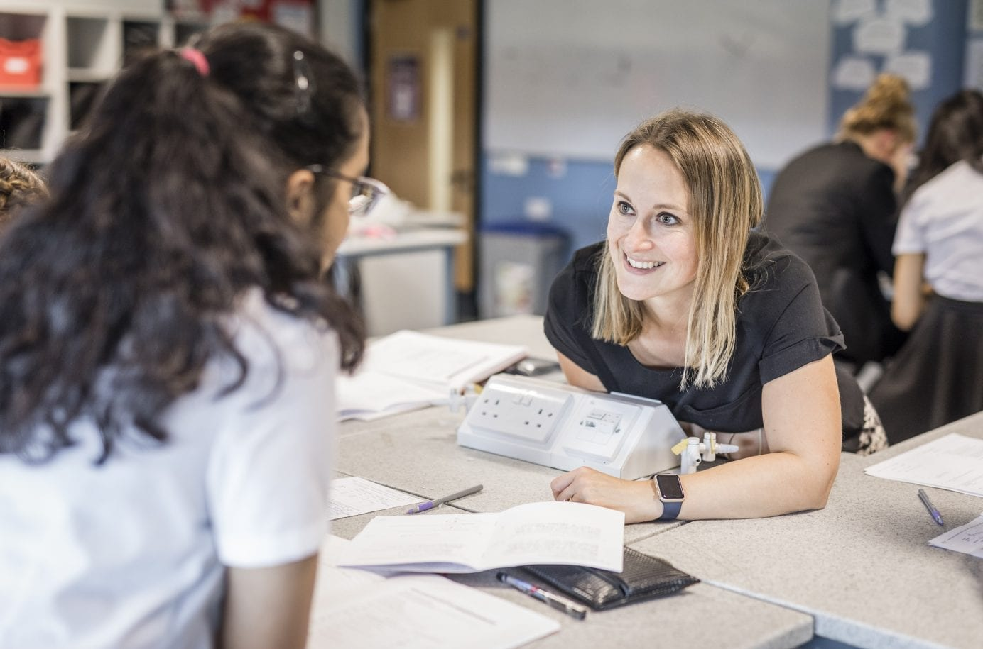 teacher smiling at her pupil, during a lesson, showing how teaching is changing