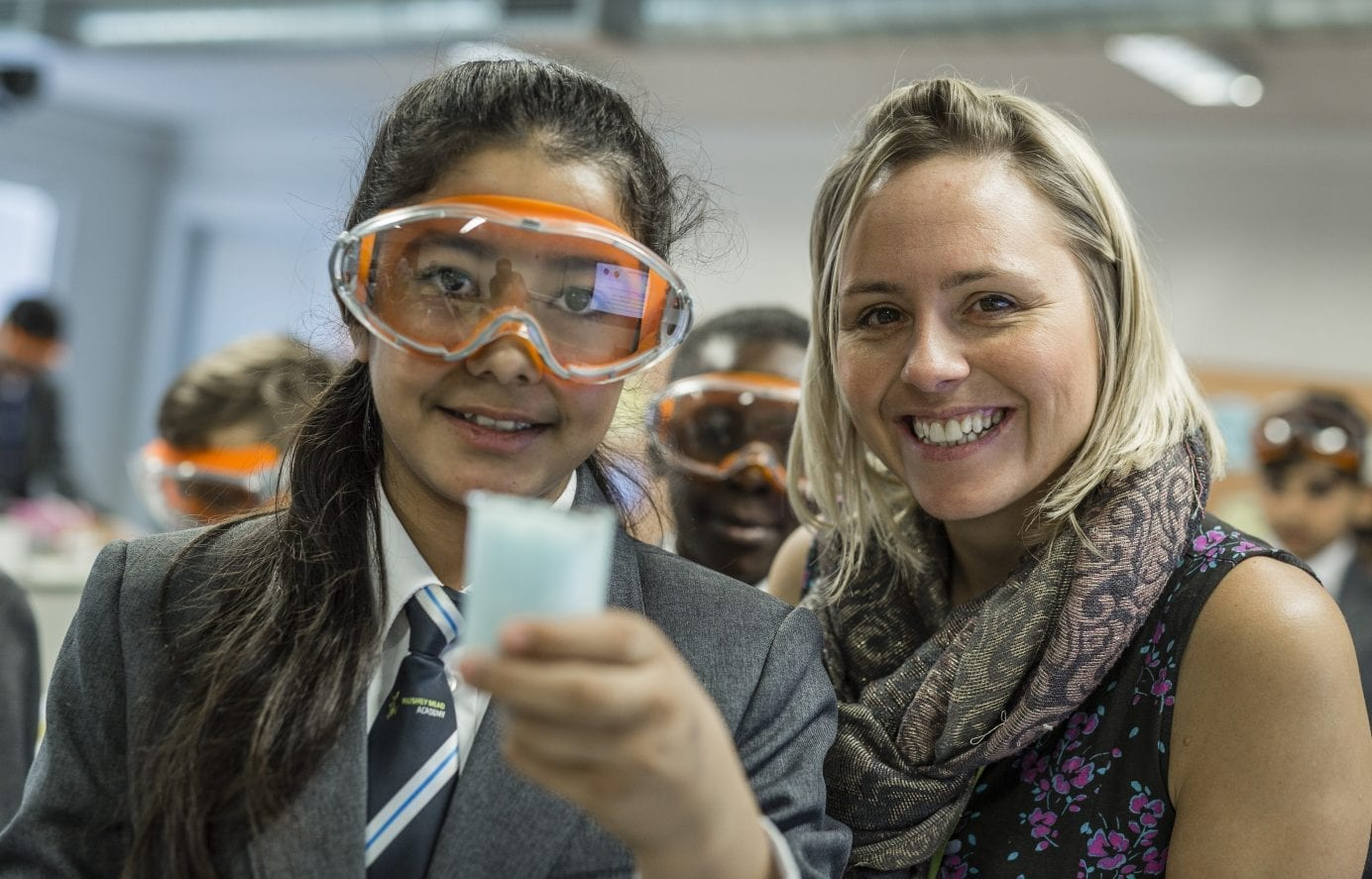A trainee teacher smiling at the camera, working with a student to make bath bombs